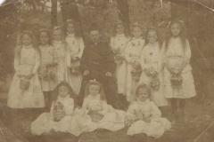 Dziewczynki sypiące kwiaty z księdzem, 1914 r.